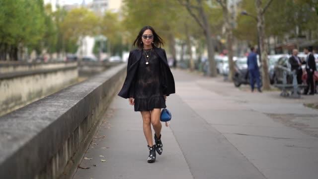 Aimee Song wears a black blazer jacket a black lace dress a blue bag outside Valentino during Paris Fashion Week Womenswear Spring/Summer 2019 on...