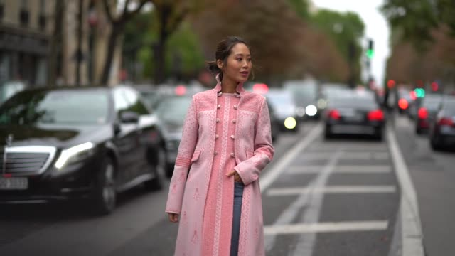 Aimee Song wears a pink coat with embroidery blue jeans outside Valentino during Paris Fashion Week Womenswear Spring/Summer 2018 on October 1 2017...
