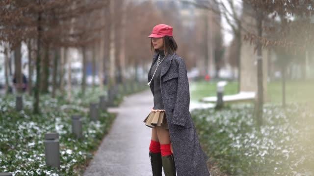 Aimee Song wears a red cap a gray coat a skirt a bag during Paris Fashion Week Womenswear Fall/Winter 2018/2019 on March 1 2018 in Paris France