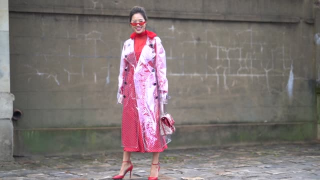 Aimee Song wears a red dress red sunglasses a bag with a printed heart a clear pvc trench coat outside Valentino during Paris Fashion Week Womenswear...