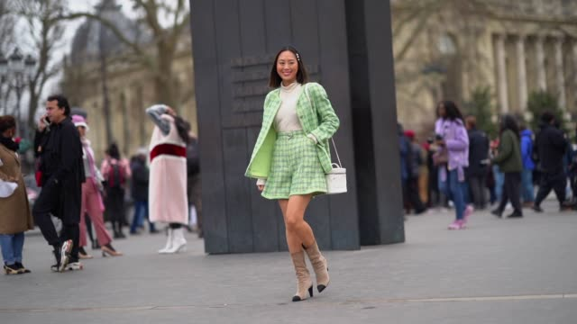 aimee song wears pearl hairpins, a white turtleneck, a green checkered tweed chanel jacket with a skirt, a white chanel bag, beige and black chanel... - dolcevita video stock e b–roll