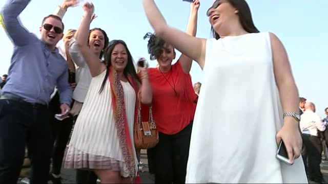 aintree ladies day 2015 england merseyside liverpool aintree racecourse ext group of women racegoers holding up drinks for camera and saying 'cheers'... - 2日目点の映像素材/bロール