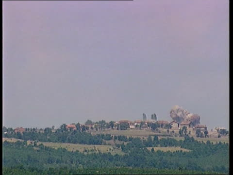 vídeos de stock e filmes b-roll de itv nightly news smoke rising in kosovo village held by the serbs and being bombarded by nato as explosion seen explosion seen in village smoke and... - ataque aéreo