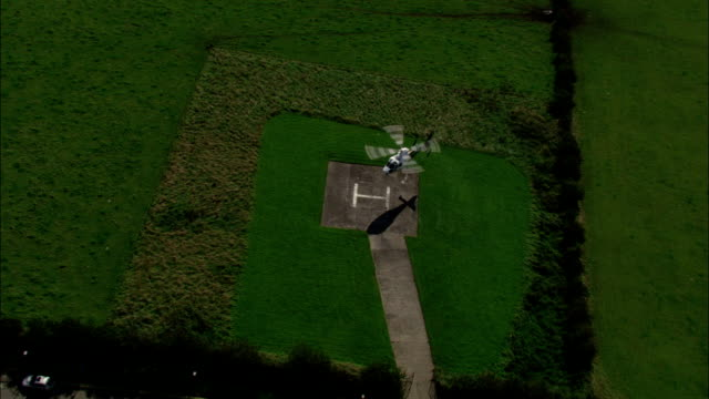 air ambulance lands on helipad by hospital. available in hd. - helicopter landing pads stock videos and b-roll footage