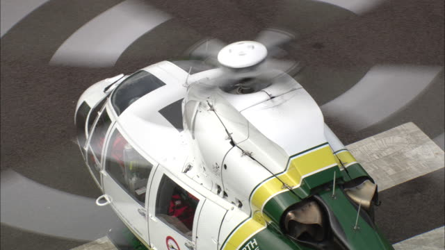 air ambulance preparing for take off on airfield available in hd. - helicopter landing pads stock videos and b-roll footage