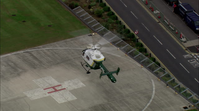 vídeos de stock, filmes e b-roll de air ambulance taking off from helipad outside hospital available in hd. - helicopter landing pads