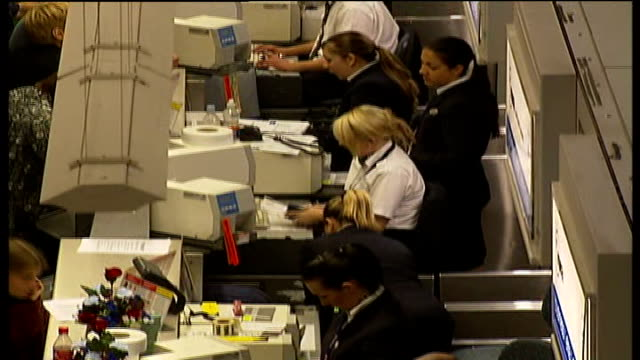 chaos at British airports and arrests made Sussex Gatwick Airport INT High angle shot of air port workers behind checkin desks TILT UP High angle...
