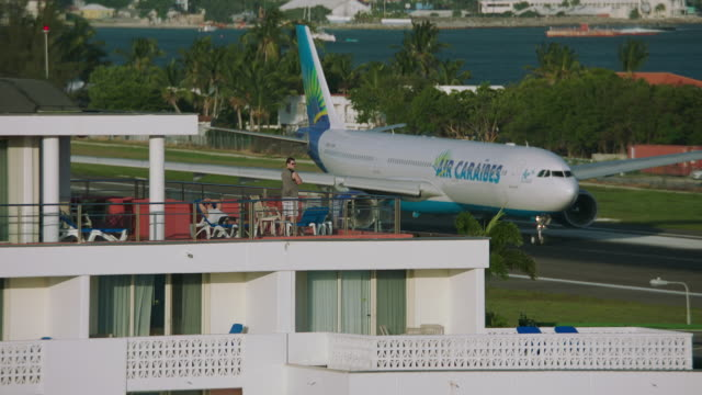 ws air caraïbes plane taxiing on taxiway in airport / st. maarten - taxiway stock-videos und b-roll-filmmaterial