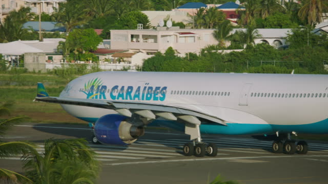 ws ts air caraïbes plane taxiing on taxiway in airport / st. maarten - taxiway stock-videos und b-roll-filmmaterial