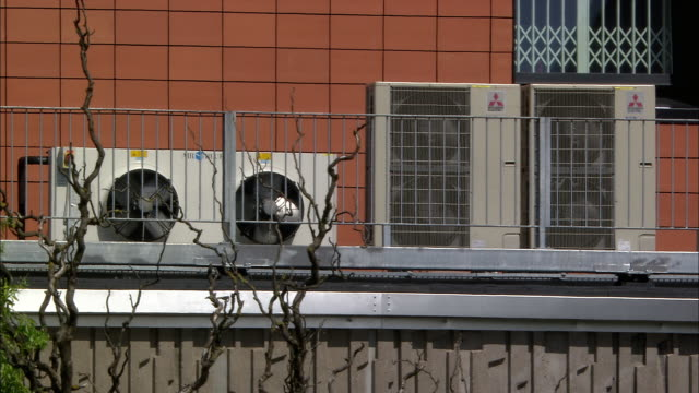 Air conditioning units on building in heat haze, Bristol, UK