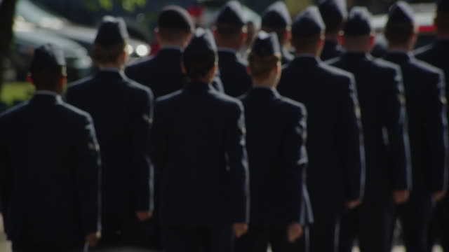 Air Force cadets march, honor guard march down the street in a small town parade.