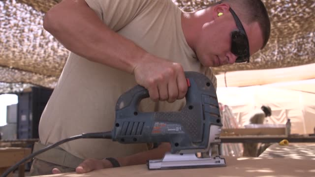 us air force civil engineers working on projects in the carpentry workshop on nigerien air base 201 agadez niger - werkzeug stock-videos und b-roll-filmmaterial