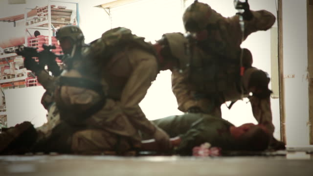 MS R/F U.S. Air Force combat search and rescue medic soldiers of  pararescue unit gives first aid to wounded pilot / Laskhar Gah, Helmand, Afghanistan
