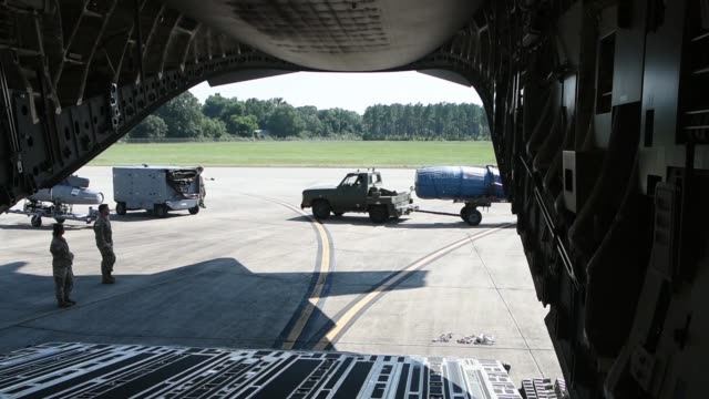 US Air Force logistics personnel from load support equipment and rolling stock cargo onto a US Air Force C17 Globemaster III large transport aircraft...