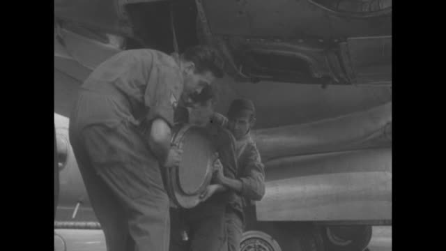 us air force mechanics stand around watching mechanic working on wheel of plane on japanese airfield during korean war/ cu man's hand working on... - bomber plane stock videos and b-roll footage