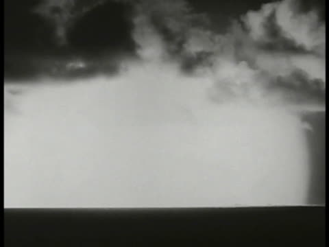air force men in uniforms eye goggles watching atomic blast test outside ws skyline nuclear explosion w/ smoke clearing cloud beginning to raise... - radioaktiver niederschlag stock-videos und b-roll-filmmaterial