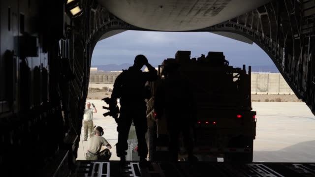 stockvideo's en b-roll-footage met us air force pilots and loadmasters with the 816th expeditionary airlift squadron marshal equipment into a c17 globemaster iii oct 31 2018 at... - kandahar afghanistan