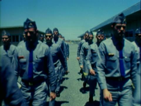 vídeos de stock, filmes e b-roll de us air force recruits in blue jumpsuits and overseas caps marching in formation / airmen marching in formation along base road - artigo de vestuário para cabeça