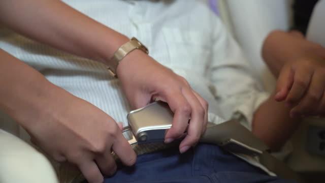 air hostess befestigen jungen sicherheitsgurt an flugzeugkabine - sicherheitsgurt sicherheitsausrüstung stock-videos und b-roll-filmmaterial