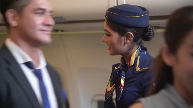 飛行機の中で空中ホステスが笑顔で乗客に挨拶 - crew点の映像素材/bロール