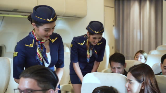 air hostess talking with passengers in the airplane - crew stock videos & royalty-free footage