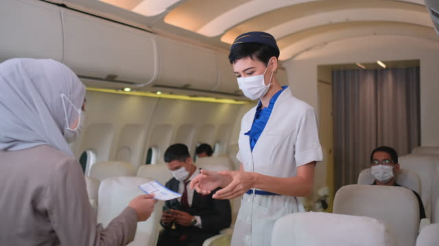 air hostess with hygiene mask check passport and boarding pass of the passenger before they take seats on airplane - aircraft carrier stock videos & royalty-free footage