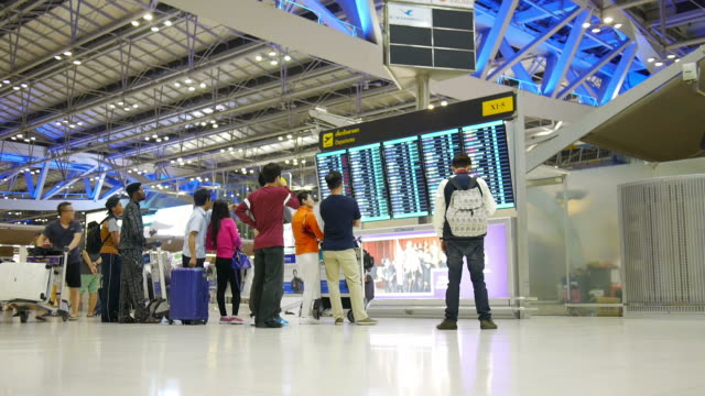 air passengers checking suvarnabhumi airport departure screens - information sign stock videos & royalty-free footage