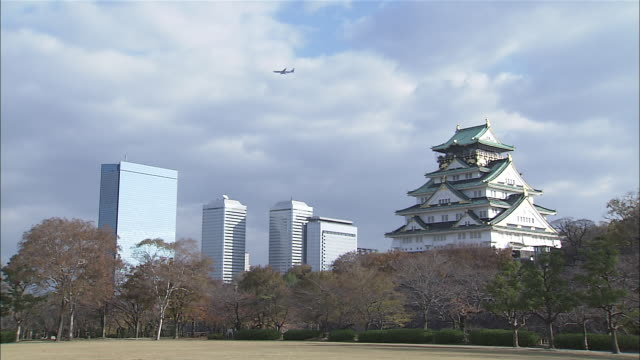 ws air plane moving over office buildings and osaka castle / osaka, japan  - japanese culture stock videos & royalty-free footage