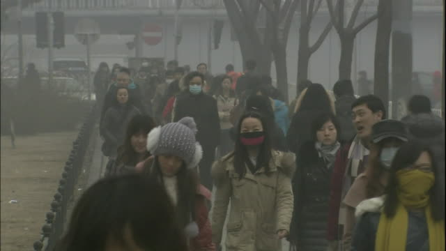 vidéos et rushes de air pollution hovers around pedestrians in beijing. - piéton