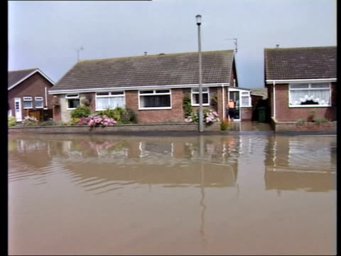 air pollution itn flooded village street pan gv people wading thru kneehigh flood water cyclist along in flooded street pull out - knee highs stock videos and b-roll footage
