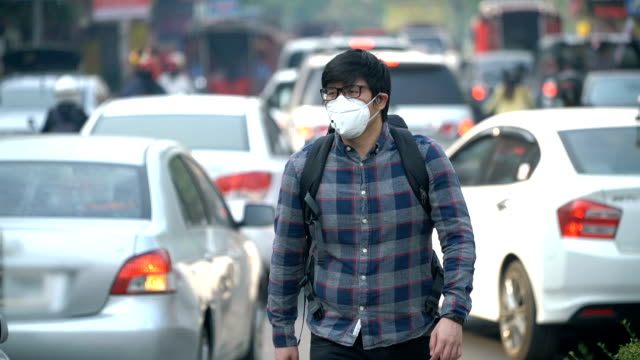 slo - mo air pollution masked asian man walking in a middle of traffic - pollution mask stock videos & royalty-free footage