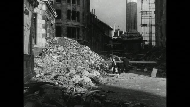 MONTAGE Air raid aftermath, with civilians heading to work among the rubble, firemen fighting fires in bombed buildings, and rubble in the streets and sidewalks / London, England, United Kingdom