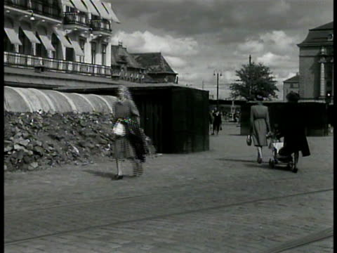 air raid shelter in front of building people riding bicycles fg women walking past air raid shelter vs people riding bicycles on street w/ trams few... - 防空壕点の映像素材/bロール
