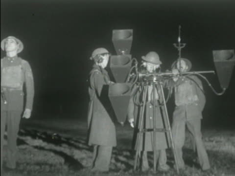 air raid siren ws antiaircraft searchlight shining upward turning soldiers holding sound locator cone shaped horns pointed up toward dark sky tu ws... - air raid siren stock videos & royalty-free footage