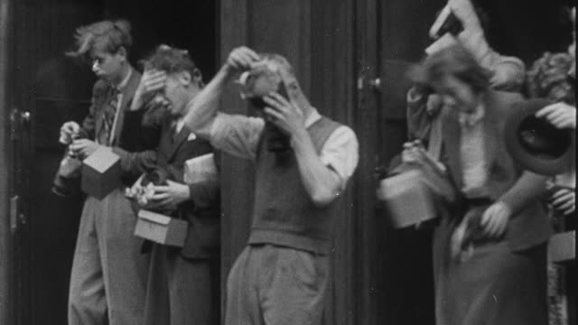 1939 MONTAGE Air raid warning ringing bell for all-clear, people removing gas masks and exiting air raid shelters and buildings, and man removing gas mask and smoking cigarette / United Kingdom