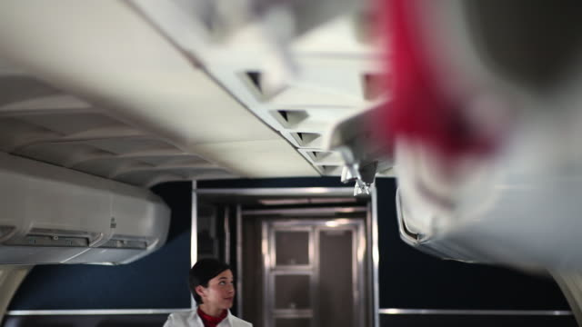 air stewardess closing overhead lockers on aeroplane - abitacolo video stock e b–roll