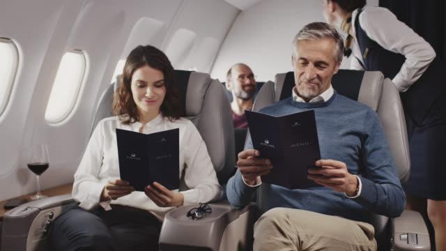 vídeos de stock, filmes e b-roll de aeromoça dando menu para pessoas de negócios - tripulação de bordo