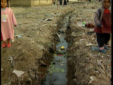 air strikes aftermath; lib iraq: basra: children playing around rubbish strewn open sewer women and children around rubbish strewn street young child... - basra video stock e b–roll