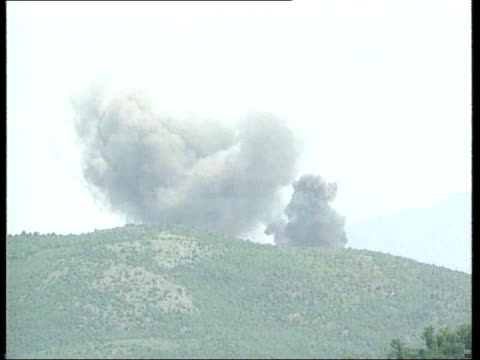 NATO air strikes / diplomacy ALBANIA / KOSOVO border EXT General views of mortar shells exploding in hills during battle between Serb forces the KLA...