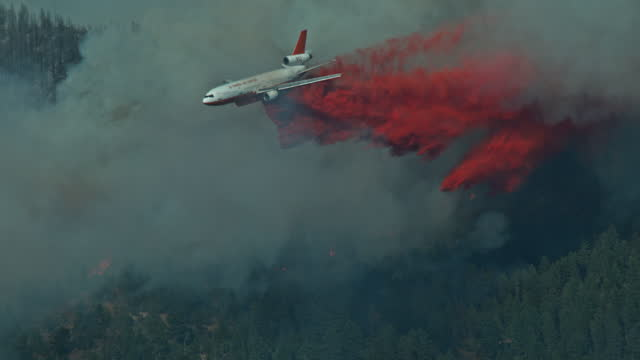 dc10 air tanker emerges from forest fire slow motion 1000 fps - 緊急用具点の映像素材/bロール