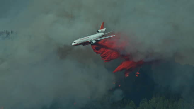 dc10 air tanker emerges from forest fire slow motion - named wilderness area stock videos & royalty-free footage