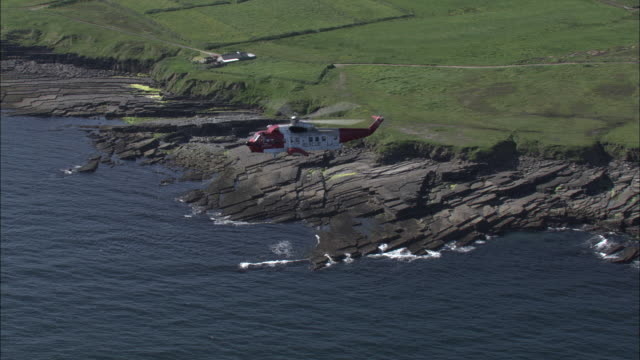 air to air shot of an irish coastguard helicopter flying over the coast of county donegal.  - coast guard stock videos and b-roll footage