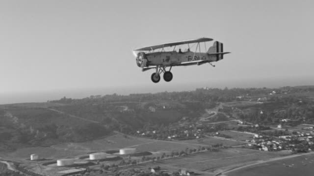 ws aerial air to air shot of biplane in flight flying over san diego coastline - air to air shot stock videos & royalty-free footage
