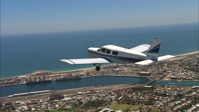 air to air shot - piper cherokee six 260 small plane flies over fremantle docks and coastline - see two container ships in dock / close up air to air... - フリーマントル点の映像素材/bロール