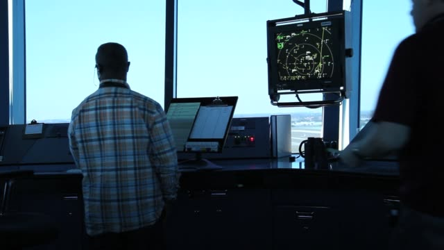 air traffic controller, david spitnale, and robert moreland work in the control tower at opa-locka airport on march 4, 2013 in opa-locka, florida.... - air traffic control tower stock videos & royalty-free footage