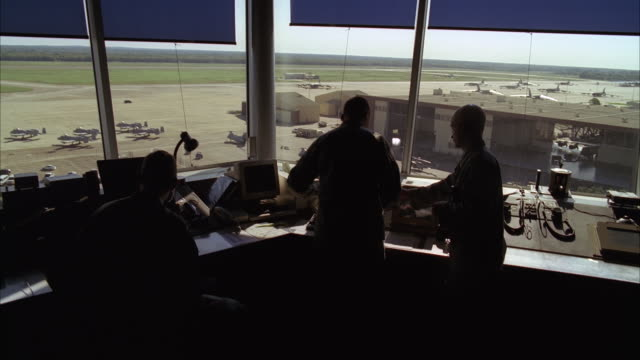 vídeos de stock, filmes e b-roll de air traffic controllers monitor aircraft activities at a military airbase. - torre de controle de tráfego aéreo