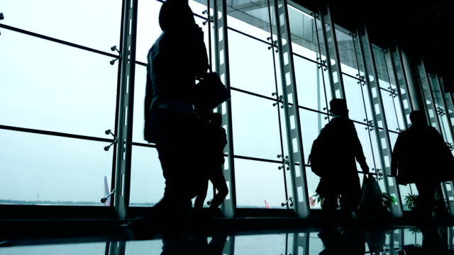 air travelers walking in corridor - passenger stock videos & royalty-free footage