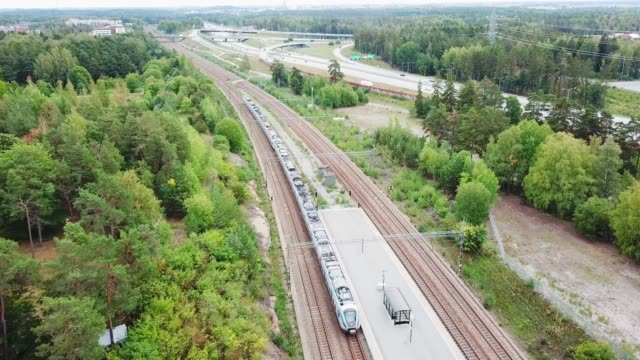 air view of departing commuter train, at trainstation helenelund, sollentuna, stockholm - commuter train stock videos & royalty-free footage