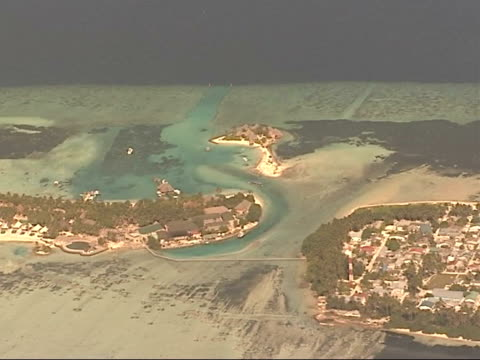 Air views of Islands Shaky camera in places Maldives Island settlement ZOOM IN to houses and beach nuts / Deserted beaches / Waves lapping against...