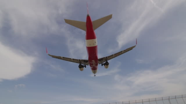 Airasia Airbus commercial airplane flying overhead on sunny blue sky and landing at Phuket airport, Thailand